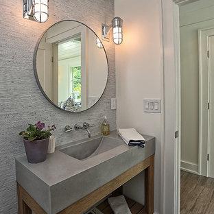 Cette image montre un WC et toilettes minimaliste de taille moyenne avec un placard en trompe-l'oeil, des portes de placard en bois vieilli, un mur gris, un sol en bois brun, un lavabo intégré et un plan de toilette en béton.