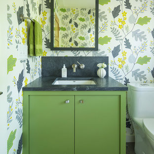 Idée de décoration pour un WC et toilettes tradition avec un placard à porte plane, des portes de placards vertess, un mur multicolore, un lavabo encastré et un sol gris.