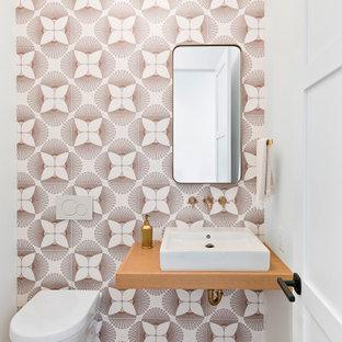 Cette image montre un WC et toilettes design de taille moyenne avec un WC suspendu, un carrelage multicolore, des carreaux de porcelaine, un mur multicolore, un sol en bois brun, une vasque, un plan de toilette en bois, un sol marron et un plan de toilette marron.
