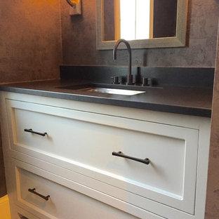 Modelo de aseo de estilo zen, pequeño, con puertas de armario grises, paredes marrones, suelo de madera en tonos medios, lavabo bajoencimera, encimera de esteatita y armarios con paneles empotrados