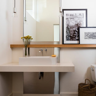 Trendy concrete floor and gray floor powder room photo in Seattle with white walls, a vessel sink, solid surface countertops and white countertops