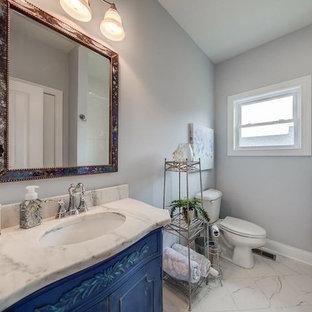 ルイビルのラスティックスタイルのおしゃれなトイレ・洗面所 (家具調キャビネット、ヴィンテージ仕上げキャビネット、グレーのタイル、磁器タイル、グレーの壁、セラミックタイルの床、アンダーカウンター洗面器、大理石の洗面台、白い床) の写真