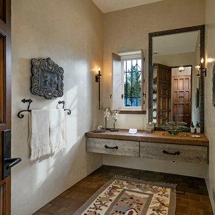 На фото: туалет среднего размера в средиземноморском стиле с бежевыми стенами, полом из терракотовой плитки и коричневым полом с