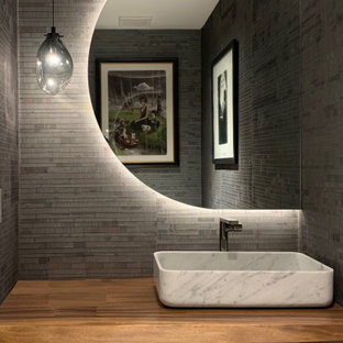 Example of a mid-sized beach style light wood floor, beige floor and wallpaper powder room design in Miami with white cabinets, a two-piece toilet, gray walls, a vessel sink, wood countertops, brown countertops and a floating vanity