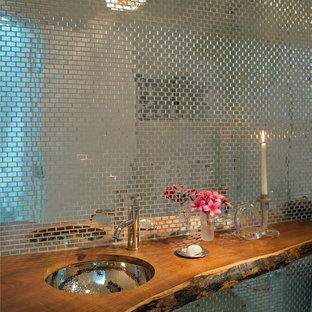 Ejemplo de aseo actual con lavabo bajoencimera, encimera de madera, baldosas y/o azulejos de metal y encimeras marrones