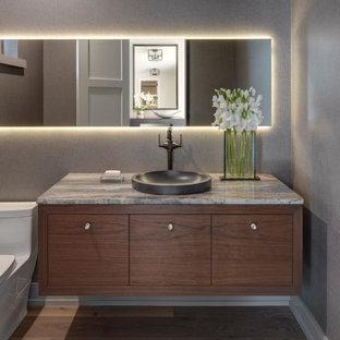 Inspiration pour un WC et toilettes vintage avec un placard à porte plane, des portes de placard en bois sombre, un WC à poser, un mur gris, un sol en bois clair, une vasque, un plan de toilette gris et du papier peint.