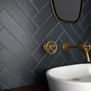 ロサンゼルスの中くらいのコンテンポラリースタイルのおしゃれなトイレ・洗面所 (黒いタイル、磁器タイル、黒い壁、ベッセル式洗面器) の写真
