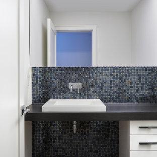 Cette image montre un WC et toilettes design de taille moyenne avec un placard à porte plane, des portes de placard blanches, un WC suspendu, un carrelage noir, des carreaux de miroir, un mur blanc, un sol en carrelage de porcelaine, une vasque, un plan de toilette en stratifié, un sol gris et un plan de toilette gris.