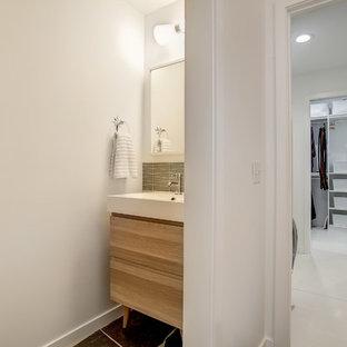 Diseño de aseo retro, de tamaño medio, con armarios con paneles lisos, puertas de armario de madera clara, paredes blancas, suelo de pizarra, lavabo integrado, encimera de cuarcita y suelo gris