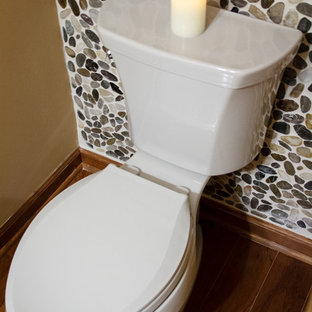 Inspiration for a small retro cloakroom in Philadelphia with a vessel sink, flat-panel cabinets, medium wood cabinets, marble worktops, a one-piece toilet, multi-coloured tiles, beige walls and pebble tiles.