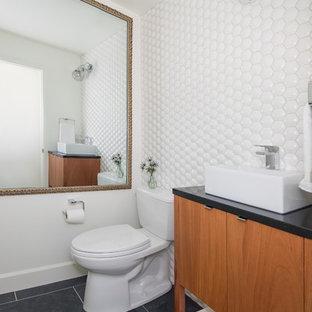 デンバーのミッドセンチュリースタイルのおしゃれなトイレ・洗面所 (家具調キャビネット、中間色木目調キャビネット、分離型トイレ、白いタイル、セラミックタイル、白い壁、スレートの床、アンダーカウンター洗面器、黒い床、黒い洗面カウンター) の写真