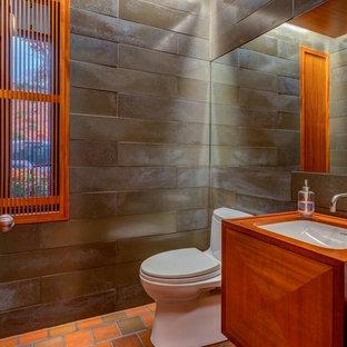 Идея дизайна: большой туалет в современном стиле с фасадами с выступающей филенкой, унитазом-моноблоком, серой плиткой, серыми стенами, полом из терракотовой плитки, врезной раковиной, столешницей из дерева, фасадами цвета дерева среднего тона и каменной плиткой