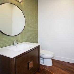 Неиссякаемый источник вдохновения для домашнего уюта: маленький туалет в стиле ретро с плоскими фасадами, темными деревянными фасадами, унитазом-моноблоком, зеленой плиткой, стеклянной плиткой, белыми стенами, темным паркетным полом, монолитной раковиной, столешницей из искусственного кварца и коричневым полом