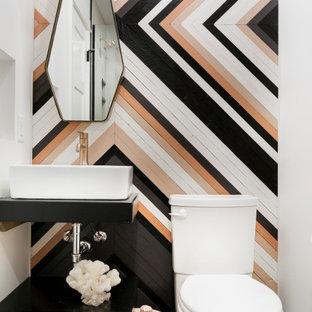 Cette image montre un WC et toilettes design avec un placard sans porte, des portes de placard noires, un WC séparé, un mur blanc, un sol en terrazzo, une vasque, un sol multicolore et un plan de toilette noir.