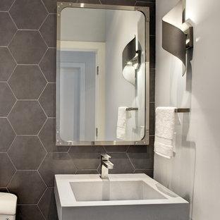 Inredning av ett 50 tals litet toalett, med en toalettstol med separat cisternkåpa, grå kakel, keramikplattor, grå väggar och ett väggmonterat handfat