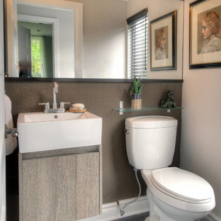 This is an example of a small contemporary cloakroom in Montreal with a wall-mounted sink, flat-panel cabinets, a two-piece toilet, grey tiles, stone tiles, brown walls, slate flooring and light wood cabinets.