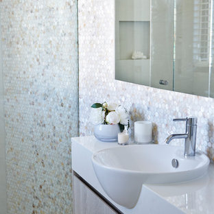 Traditional cloakroom in Sydney with flat-panel cabinets, light wood cabinets, multi-coloured tiles, mosaic tiles, white walls, porcelain flooring, an integrated sink and solid surface worktops.