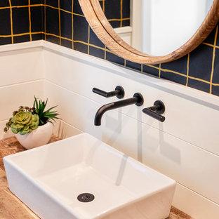 Idées déco pour un WC et toilettes campagne avec un placard en trompe-l'oeil, des portes de placard en bois brun, un WC à poser, un mur noir, un sol en vinyl, une vasque, un plan de toilette en bois et un plan de toilette marron.