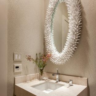 Пример оригинального дизайна: маленький туалет в современном стиле с плоскими фасадами, светлыми деревянными фасадами, бежевой плиткой, бежевыми стенами, полом из керамической плитки, накладной раковиной и столешницей из травертина