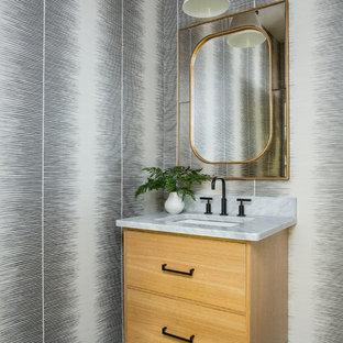 Exemple d'un WC et toilettes moderne avec un placard à porte plane, des portes de placard en bois clair, un sol en carrelage de terre cuite, un lavabo encastré, un plan de toilette en marbre, un sol turquoise et un plan de toilette gris.