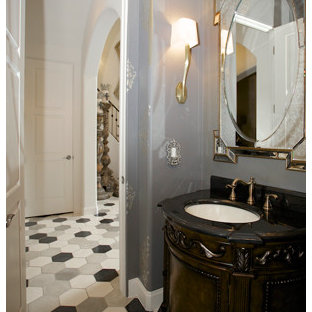 This is an example of a classic cloakroom in Dallas with multi-coloured tiles, freestanding cabinets, dark wood cabinets, concrete flooring, a submerged sink, marble worktops and grey walls.