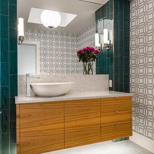 На фото: туалеты в современном стиле с плоскими фасадами, зеленой плиткой, настольной раковиной, фасадами цвета дерева среднего тона и серым полом