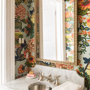 Example of an eclectic powder room design with multicolored walls, a console sink and marble countertops
