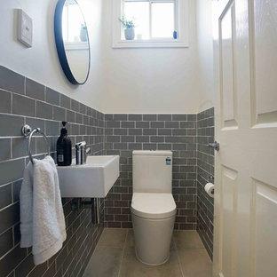 Пример оригинального дизайна: туалет в стиле современная классика с раздельным унитазом, серой плиткой, плиткой кабанчик, белыми стенами, подвесной раковиной и серым полом