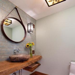 Свежая идея для дизайна: туалет среднего размера в стиле современная классика с унитазом-моноблоком, синей плиткой, плиткой кабанчик, синими стенами, паркетным полом среднего тона, настольной раковиной и столешницей из дерева - отличное фото интерьера