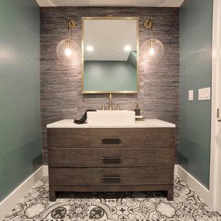 Imagen de aseo actual con armarios tipo mueble, puertas de armario de madera en tonos medios, paredes verdes, lavabo sobreencimera, suelo multicolor y encimeras blancas
