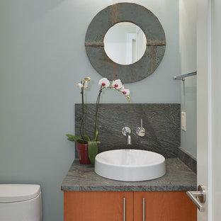 На фото: маленькие туалеты в современном стиле с плоскими фасадами, фасадами цвета дерева среднего тона, унитазом-моноблоком, синими стенами, настольной раковиной и разноцветной столешницей