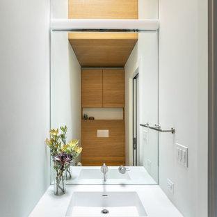Kleine Moderne Gästetoilette mit flächenbündigen Schrankfronten, weißen Schränken, Wandtoilette, weißer Wandfarbe, integriertem Waschbecken, Mineralwerkstoff-Waschtisch, weißer Waschtischplatte, eingebautem Waschtisch und Holzdecke in San Francisco