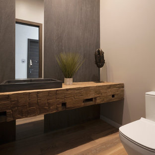 Example of a mid-sized minimalist gray tile and stone slab medium tone wood floor and beige floor powder room design in Chicago with medium tone wood cabinets, a one-piece toilet, beige walls, a vessel sink, wood countertops and beige countertops