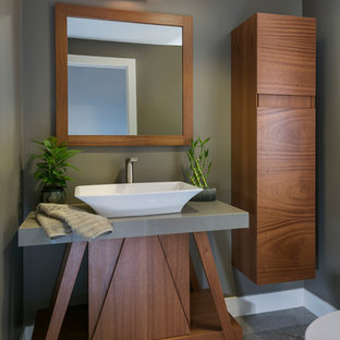 This is an example of a small world-inspired cloakroom in Boston with flat-panel cabinets, dark wood cabinets, a one-piece toilet, grey walls, slate flooring, a vessel sink, limestone worktops, grey floors and grey worktops.