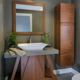 Пример оригинального дизайна: маленький туалет в восточном стиле с плоскими фасадами, темными деревянными фасадами, унитазом-моноблоком, серыми стенами, полом из сланца, настольной раковиной, столешницей из известняка, серым полом и серой столешницей
