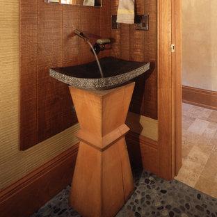 Пример оригинального дизайна: маленький туалет в восточном стиле с настольной раковиной, фасадами цвета дерева среднего тона, бежевыми стенами, полом из галечной плитки, столешницей из бетона и раздельным унитазом