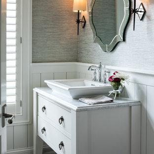 Modelo de aseo marinero con armarios tipo mueble, puertas de armario blancas, paredes grises, suelo de madera oscura, lavabo sobreencimera, suelo marrón y encimeras blancas