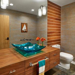 Mittelgroße Maritime Gästetoilette mit flächenbündigen Schrankfronten, hellbraunen Holzschränken, brauner Wandfarbe, Schieferboden, Aufsatzwaschbecken, Waschtisch aus Holz, braunem Boden und brauner Waschtischplatte in Minneapolis