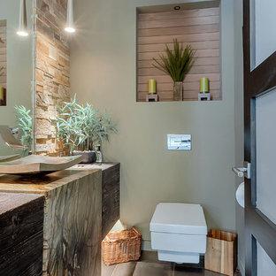 Idées déco pour un petit WC et toilettes contemporain avec un WC suspendu, un carrelage de pierre, un sol en carrelage de céramique, une vasque, un plan de toilette en granite, un sol marron, un carrelage beige, un mur vert et un placard à porte plane.