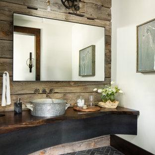 На фото: туалет в стиле рустика с белыми стенами, настольной раковиной, столешницей из дерева и черным полом с