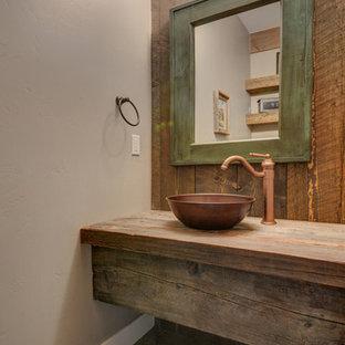 アルバカーキのラスティックスタイルのおしゃれなトイレ・洗面所 (一体型トイレ、グレーの壁、磁器タイルの床、ベッセル式洗面器、木製洗面台、ブラウンの洗面カウンター) の写真