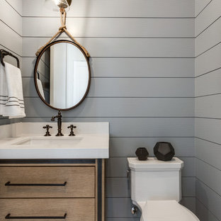 Photo of a country powder room in Salt Lake City with flat-panel cabinets, medium wood cabinets, grey walls, an undermount sink and white benchtops.