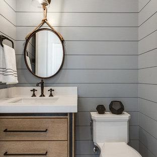 Landhaus Gästetoilette mit flächenbündigen Schrankfronten, hellbraunen Holzschränken, grauer Wandfarbe, Unterbauwaschbecken und weißer Waschtischplatte in Salt Lake City