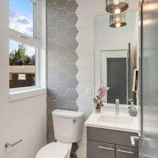 Esempio di un bagno di servizio design con ante lisce, ante grigie, piastrelle grigie, pareti bianche, pavimento in legno massello medio, lavabo sottopiano, pavimento marrone e top bianco