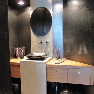 Неиссякаемый источник вдохновения для домашнего уюта: туалет среднего размера в стиле модернизм с плоскими фасадами, светлыми деревянными фасадами, унитазом-моноблоком, серой плиткой, бежевой плиткой, керамогранитной плиткой, черными стенами, полом из керамогранита, настольной раковиной и столешницей из дерева