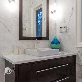 Aménagement d'un petit WC et toilettes contemporain avec un placard à porte plane, des portes de placard noires, un plan de toilette en quartz modifié, un carrelage blanc, un sol en carrelage de céramique et un carrelage de pierre.