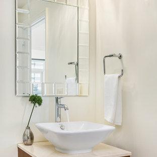 シアトルの小さいコンテンポラリースタイルのおしゃれなトイレ・洗面所 (フラットパネル扉のキャビネット、濃色木目調キャビネット、白い壁、ベッセル式洗面器、ライムストーンの洗面台) の写真