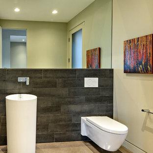 Идея дизайна: туалет среднего размера в современном стиле с инсталляцией, серой плиткой, керамогранитной плиткой, бежевыми стенами, бетонным полом, раковиной с пьедесталом, столешницей из искусственного кварца и серым полом