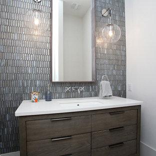 Foto di un bagno di servizio moderno di medie dimensioni con consolle stile comò, ante grigie, WC sospeso, piastrelle grigie, piastrelle di vetro, pareti bianche, pavimento con piastrelle in ceramica, lavabo sottopiano, top in superficie solida e pavimento grigio
