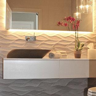 Réalisation d'un petit WC et toilettes minimaliste avec un placard à porte plane, des portes de placard beiges, un carrelage gris, des carreaux de porcelaine, un mur gris, un sol en carrelage de porcelaine et une vasque.